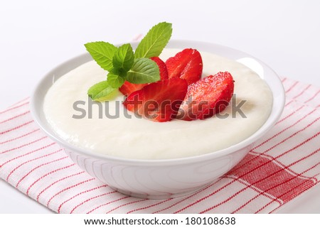 Swemolina pudding in a bowl with fresh strawberries