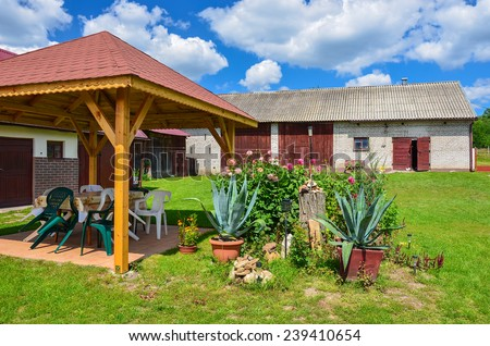 SWIETOKRZYSKIE VOIVODSHIP, POLAND - AUG 4, 2011: farm house in rural area of Poland on sunny summer day. Agriculture is important part of country's economy, 40% of population lives in non urban areas. - stock photo