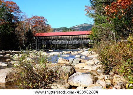 Swift River and old covered bridge at autumn in White Mountain National Forest, New Hampshire, USA. - stock photo