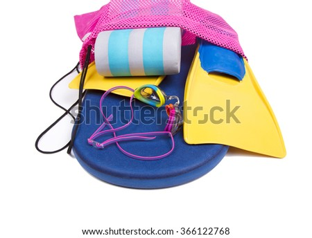 Swim fins, kick board, pull buoy and goggles spilling out of a bag on a isolated white background for high school swim team background or competitive swim teams.  - stock photo