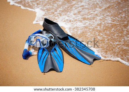 Swim flippers, mask, snorkel in the surf on the sandy beach; selective focus - stock photo