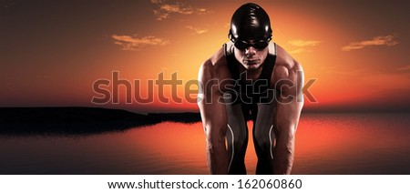 Swimmer muscled triathlon man with cap and glasses outdoor at a lake at sunset. Extreme fitness sport. Panorama shot.