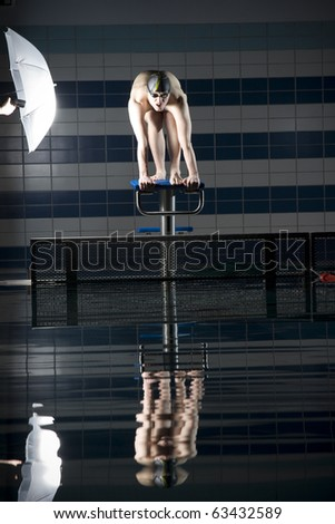 Swimmer on starting bar Illuminated by umbrella - stock photo