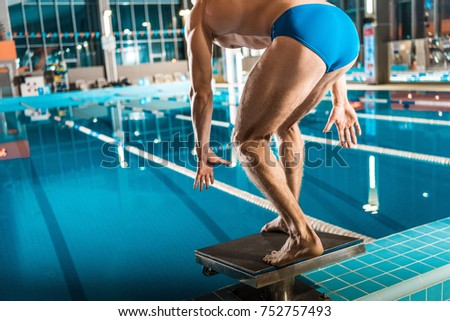 Awesome Swimmer Standing On Diving Board Ready To Jump Into Competition Swimming  Pool
