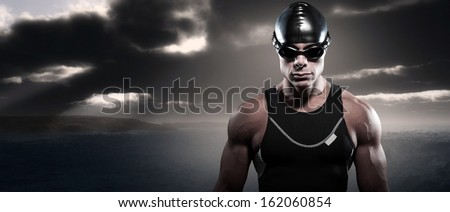 Swimmer triathlon man with cap and glasses outdoor at rough sea with stormy dark sky. Extreme fitness sport.
