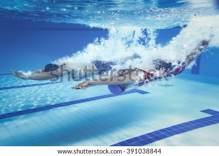 swimmer woman Jump from platform jumping a swimming pool.Underwater photo - stock photo