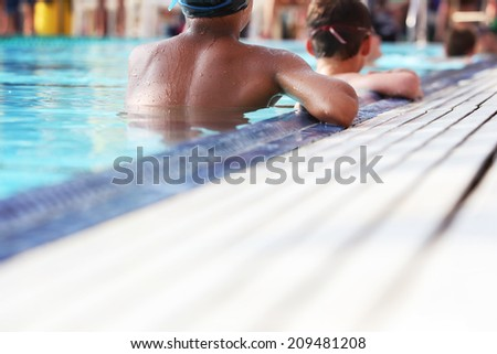 Swimmers waiting at the edge of the pool - stock photo