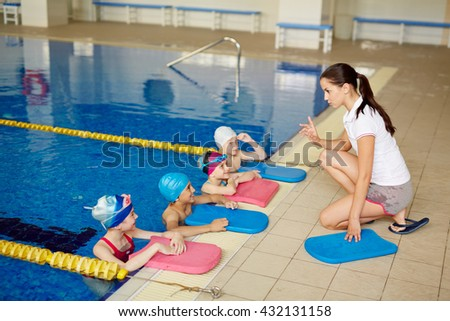 Swimming class listening to the coach - stock photo