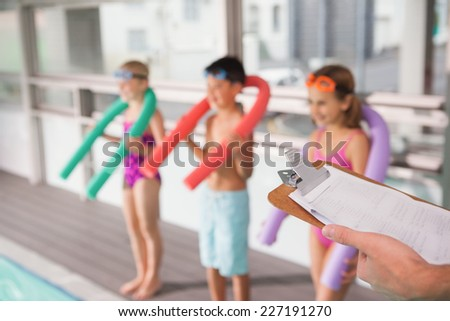 Swimming coach holding clipboard poolside at the leisure center - stock photo