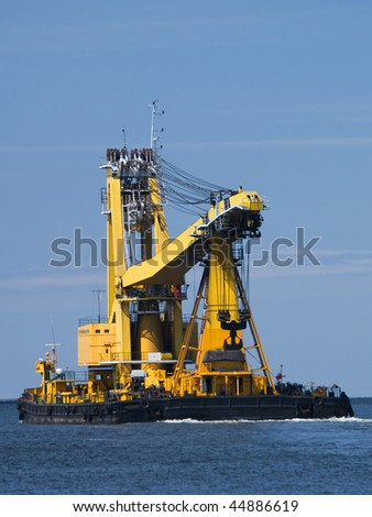 Swimming crane transporting another crane to a dock - stock photo