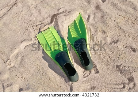 Swimming fins on a beach - stock photo