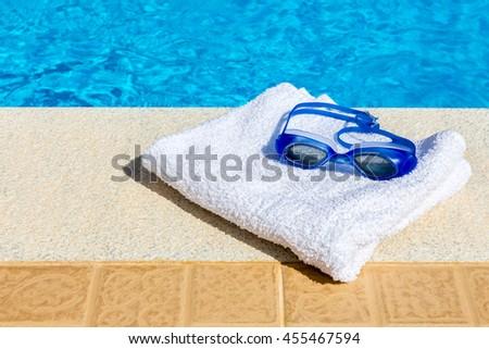 Swimming goggles and bath towel near blue swimming pool - stock photo