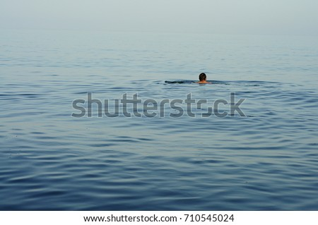 Swimming man. Nature and humans. Water blue. Small waves. Summer holiday.