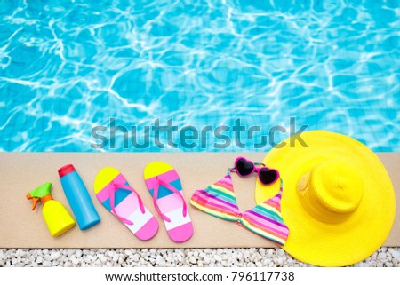 Swimming pool accessories flat lay. Top view of beach items on pool deck. Flip flops, bikini and hat, sun glasses. Water toys. Summer vacation in tropical resort. Copy space. Colorful beach wear.