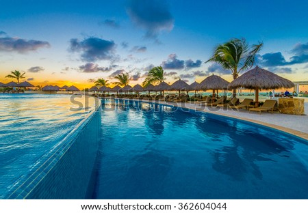 Swimming pool and a grass beach umbrellas with lounges at night, dawn, evening time. Mexico.