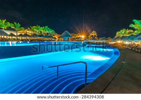 Swimming pool and a grass beach umbrellas with lounges at night, dawn time. Mexico. - stock photo