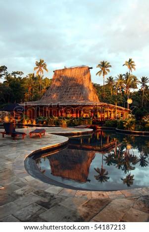 Swimming pool and bar-hut in tropical resort.  Beautiful sunset - stock photo