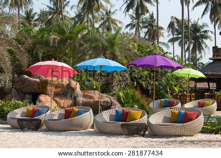 Swimming pool and beach chairs in a tropical garden, Thailand - stock photo