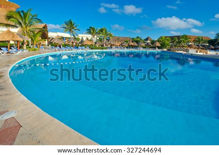 Swimming pool and lounges and a bungalow at the luxury caribbean, mexican resort.