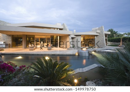 Swimming pool and modern house exterior against the sky - stock photo