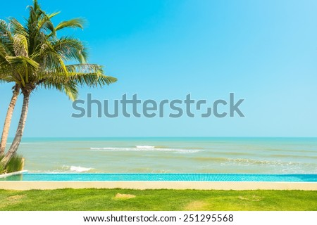 Swimming pool and Palm tree on beach - stock photo