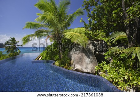 Swimming pool and palm trees of the Banyan Tree Hotel, Anse Intendance, Mahe', Seychelles - stock photo