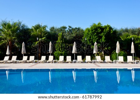 Swimming pool and seven not opened umbrellas - stock photo