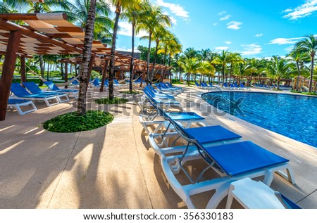 Swimming pool and some lounges at the tropical, caribbean resort.