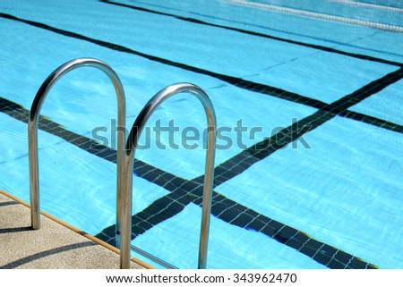 Swimming pool and stainless stair with blue tile lanes