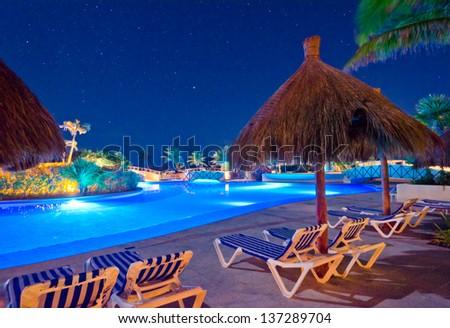 Swimming pool at a luxury caribbean resort at night, dawn time. Bahia Principe, Mexican Resort. - stock photo