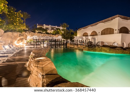 Swimming pool at night illumination and luxury buildings behind it - stock photo