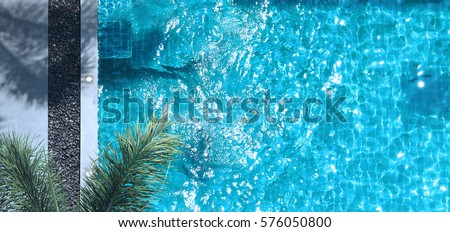 swimming pool blue water in summer and white beach beds and top view angle