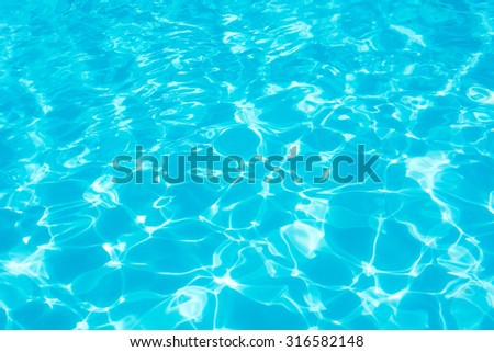 Swimming pool blue water reflecting the sun rippled details.