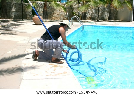 Swimming pool cleaner during his work.