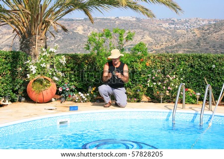Swimming pool cleaner during his work. - stock photo