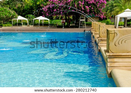 Swimming pool decorated with a fountain. - stock photo