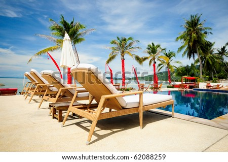 Swimming pool facing the lagoon in a tropical hotel , with coconut & beach , Samui, Thailand - stock photo