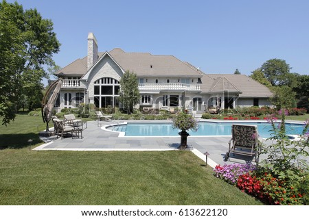 Swimming pool in back of luxury home with blue stone deck.