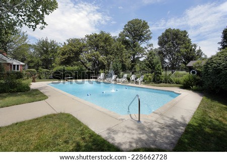 Swimming pool in suburban home with golf course view - stock photo