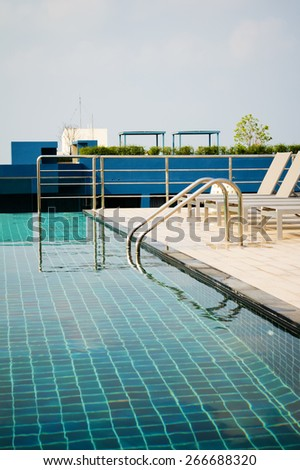 Swimming pool on top of roof deck building. - stock photo