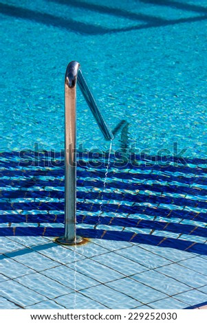 Swimming pool stairs with hand-rail on water background. - stock photo