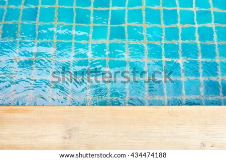 Swimming pool top view, Wooden on blue pool for design, Waves hit the edge of pool - stock photo