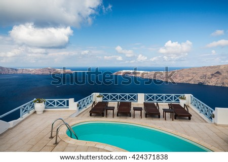 Swimming pool with a view from the top of the Santorini island, Greece. - stock photo