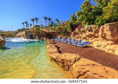 Swimming pool with artificial waterfall and sun loungers - stock photo