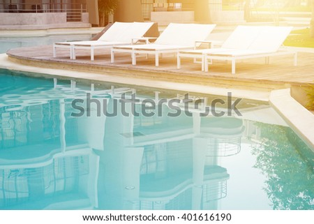Swimming pool with beach chairs in resort. - stock photo