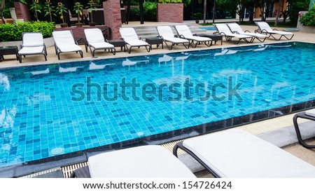 Swimming pool with black beach chairs