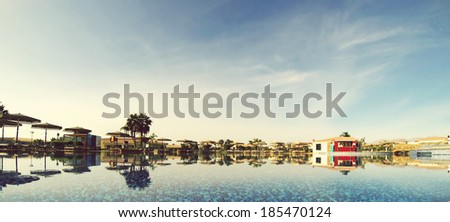 Swimming pool with blue water on the background of sky and palm trees - stock photo