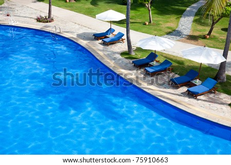 Swimming pool with chaise lounge and sunshade at tropical resort - stock photo