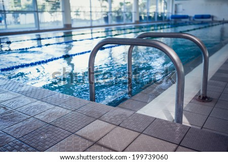 Swimming pool with hand rails at the leisure center - stock photo