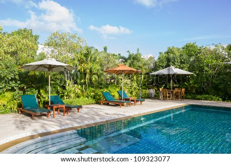 Swimming pool with relaxing seats and sun umbrella